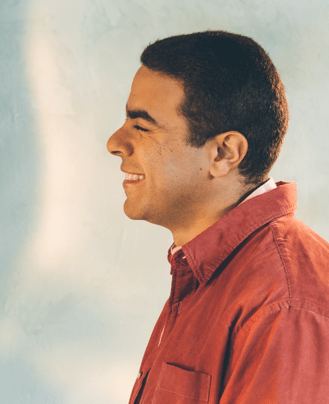 Photo: Portrait of young man smiling, wearing a red button up.